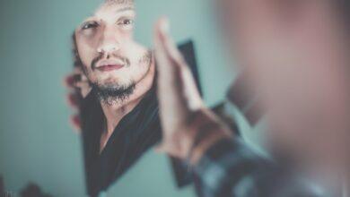 Image of man looking into broken mirror