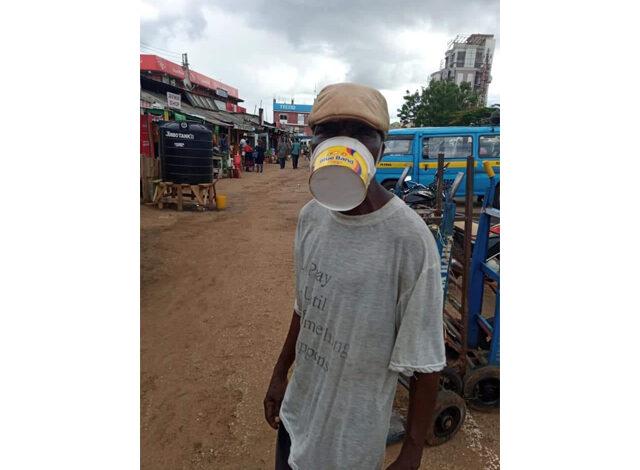 Image of man wearing ice cream carton as mask