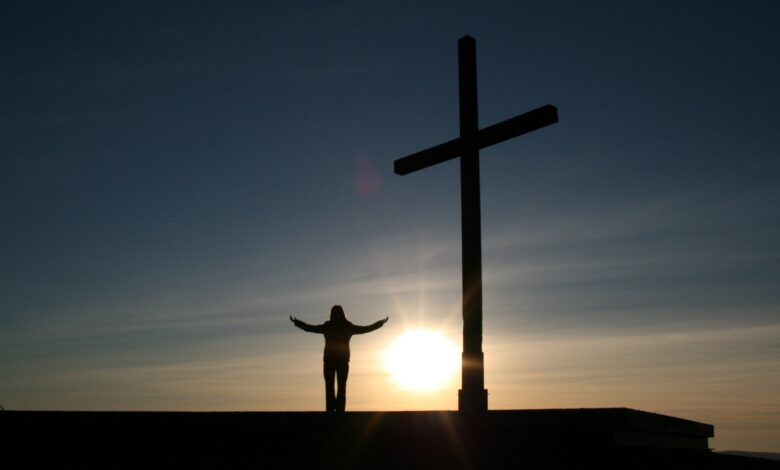 Person standing next to cross at sunrise