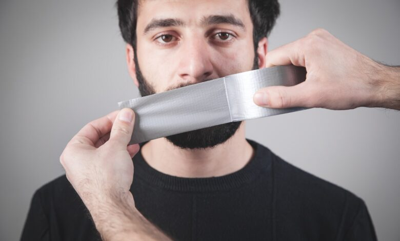 Image of man having tape applied over his mouth