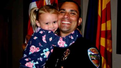 Police officer Brian Zach hugs his newly-adopted daughter