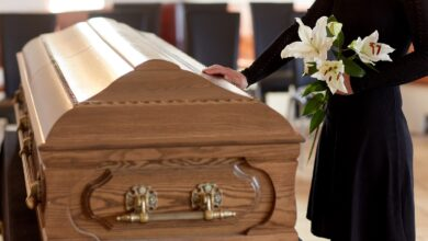 Image of woman holding flowers and touching a casket