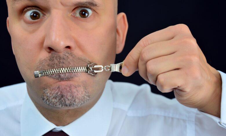 Image of man zipping his mouth shut