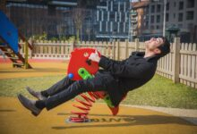 Image of adult man playing on child's playground toy
