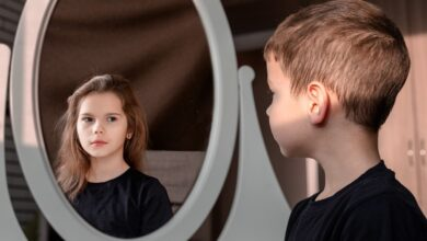 A picture of a boy looking into a mirror and seeing a girl's face.