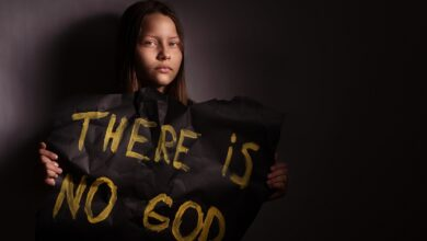 """Image of athiest teen holding sign saying """"There is no God"""""""